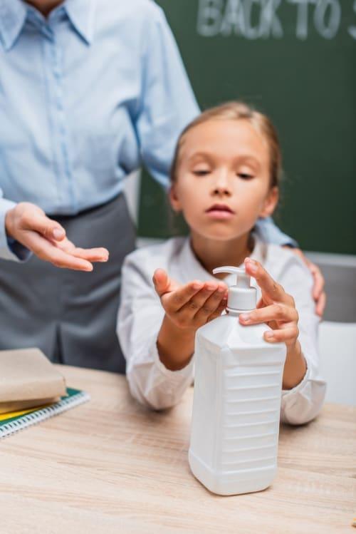 toxic hand sanitizers warning, girl using hand sanitizer