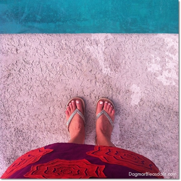 feet with flip flops close to pool edge
